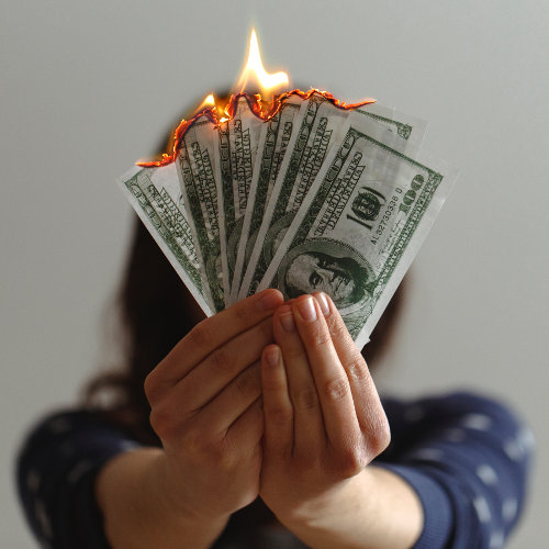 Hands holding burning 100 dollar bills - Photo by Jp Valery on Unsplash